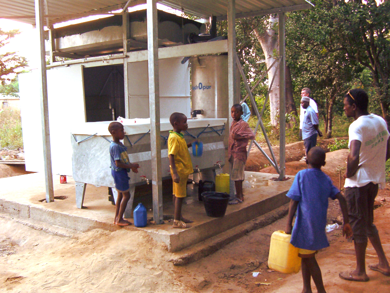 Villageois guinéens s'alimentant en eau potable auprès d'une installation HYDROPUR. Guinean villagers drawing drinking water from a HYDROPUR unit.