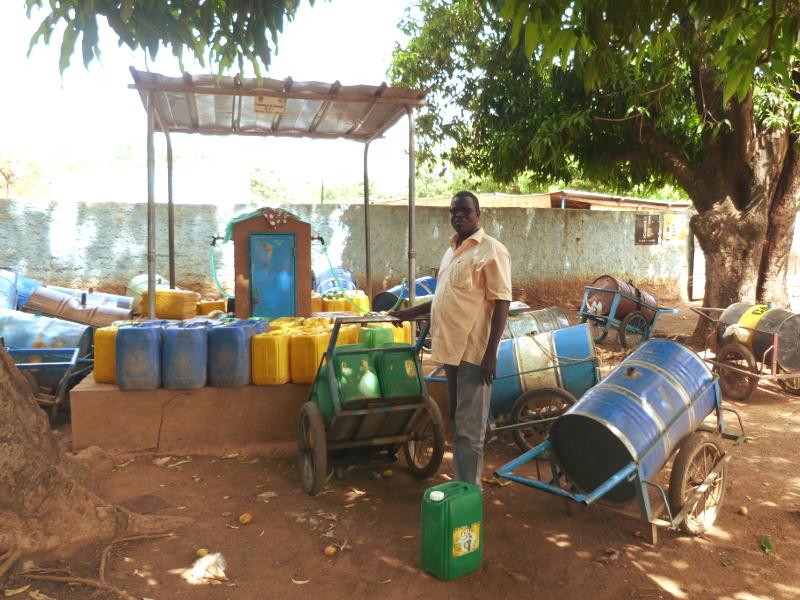 Jean-Christophe KI, Directeur Général de VERGNET BURKINA, auprès d'une borne fontaine prise en gestion sur la commune rurale de Kampti (Région Sud-Ouest).