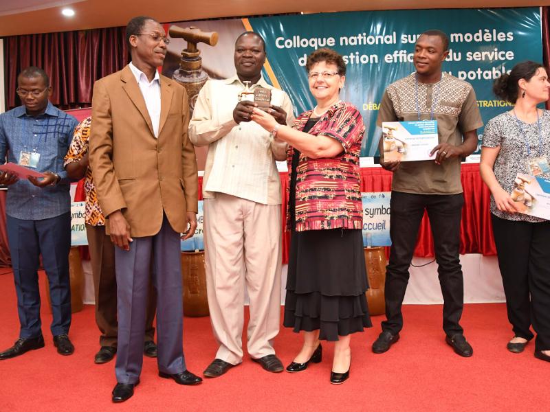 Anne VINCENT, Représentante Résidente de l'UNICEF au Burkina Faso, et André Patindé NONGUIERMA, Directeur Général de l'Assainissement, représentant le Ministre de l'Eau et de l'Assainissement du Burkina Faso, remettent à Samuel SAWADOGO et Abdoulaye SORY (VERGNET BURKINA) le 1er prix du marché des innovateurs dans le cadre du Colloque national sur les modèles de gestion efficace du service d'eau potable, le 19 octobre 2017 à Ouagadougou. Crédits photo: SESAME PICTURES.